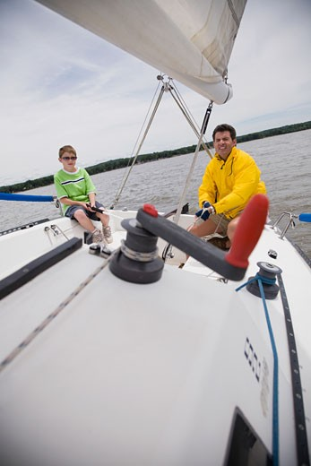 Father and son sitting on sailboat : Stock Photo