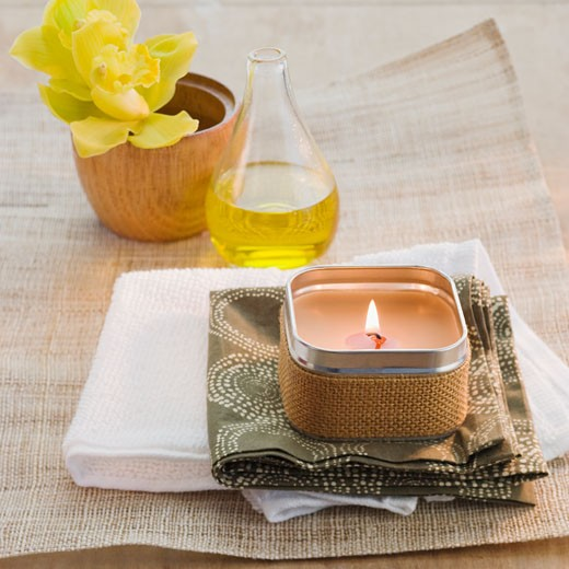 Lit candle in front of flower and bath oil : Stock Photo