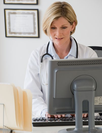 Female doctor typing on computer : Stock Photo