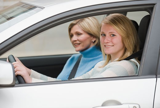 Teenaged girl driving with mother : Stock Photo