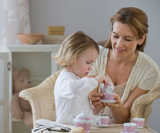 Mother and daughter playing with tea set : Stock Photo