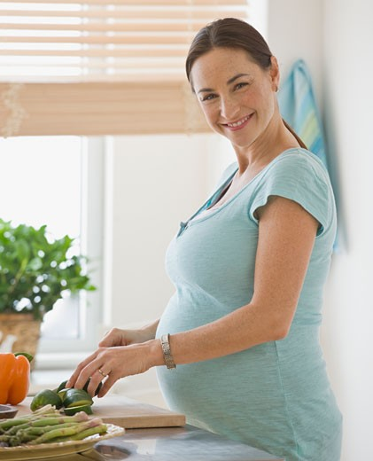 Pregnant Hispanic woman chopping vegetables : Stock Photo