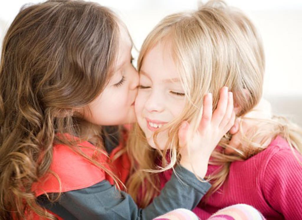 Girl kissing sister on cheek : Stock Photo