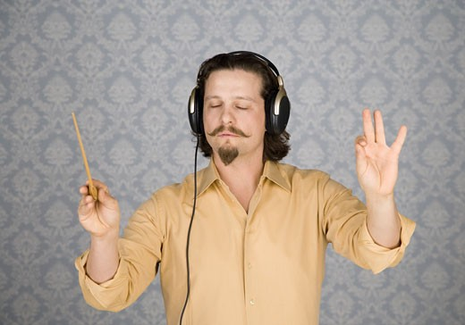 Man listening to headphones and conducting : Stock Photo