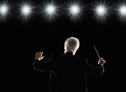 Man in tuxedo conducting under lights : Stock Photo