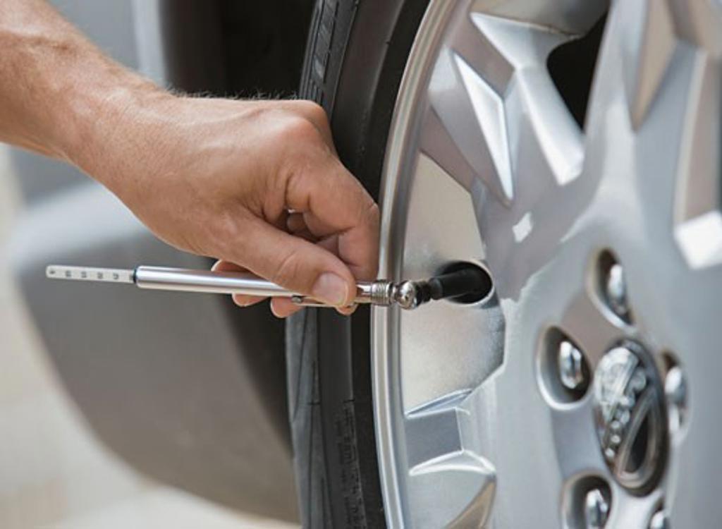 Stock Photo: 1795R-15684 Man checking car tire pressure