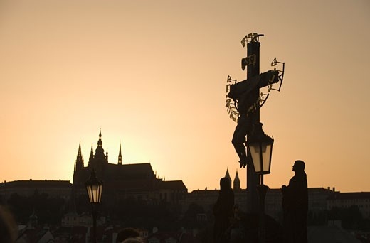 Silhouetted crucifix and cathedral : Stock Photo