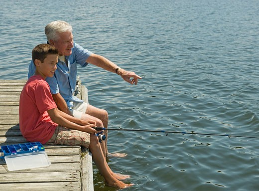 Stock Photo: 1795R-16031 Grandfather and grandson fishing off dock