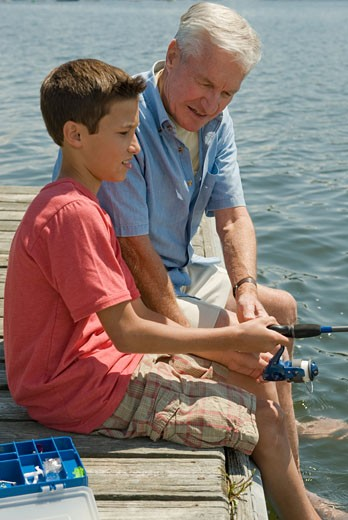 Stock Photo: 1795R-16032 Grandfather and grandson fishing off dock
