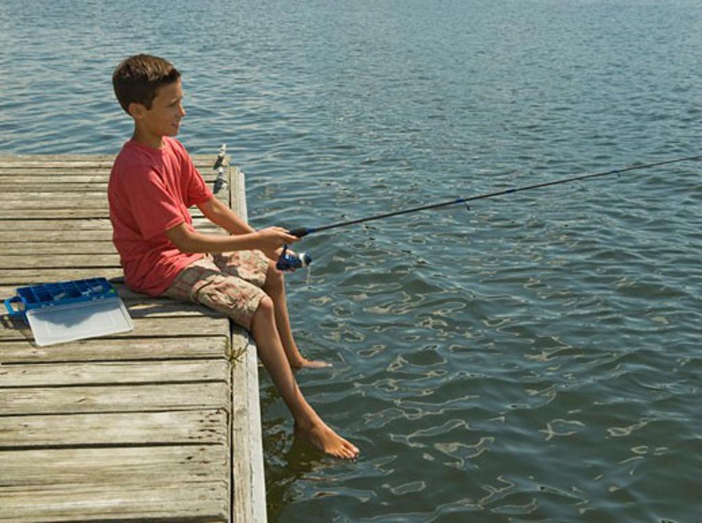 Boy fishing off dock : Stock Photo