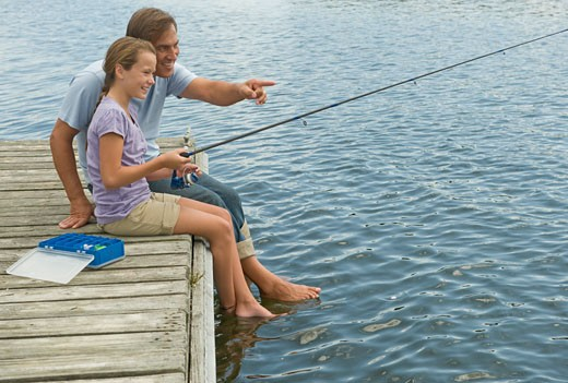 Stock Photo: 1795R-16039 Father and daughter fishing off dock