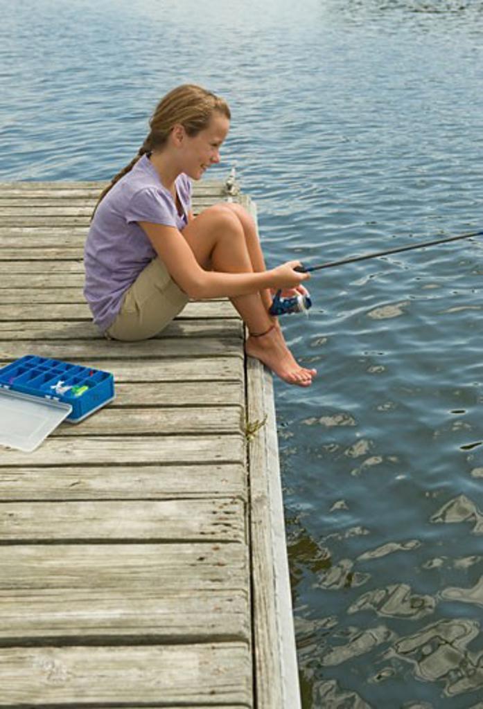 Girl fishing off dock : Stock Photo