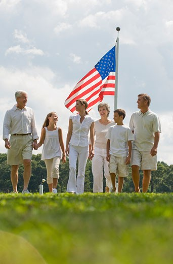 Multi-generational family walking in front of American flag : Stock Photo