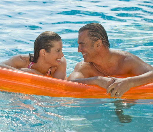 Stock Photo: 1795R-16064 Couple resting on raft in swimming pool