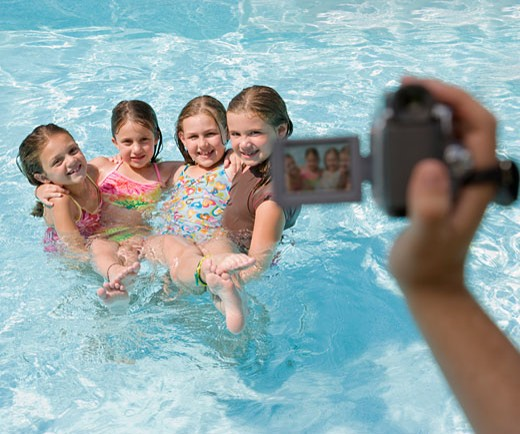 Stock Photo: 1795R-16087 Girls being videotaped in swimming pool