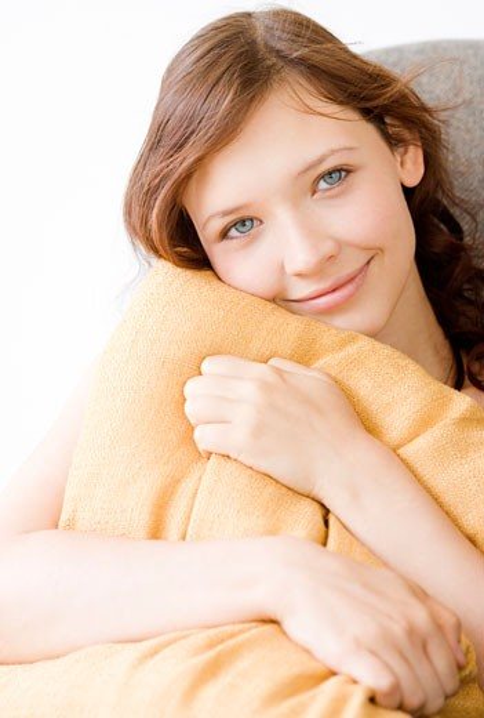 Teenage girl hugging pillow : Stock Photo