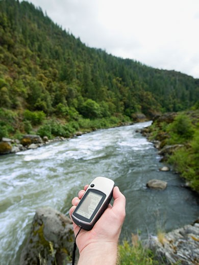 Man holding gps unit by river : Stock Photo