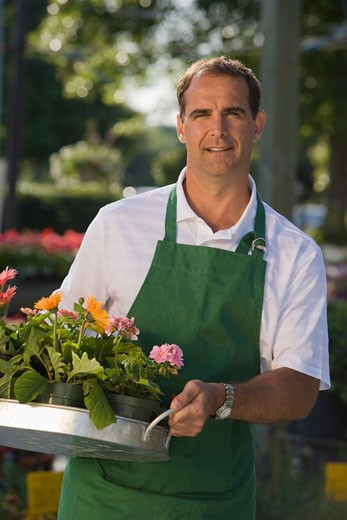 Man working in garden center : Stock Photo