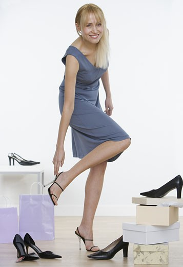 Woman putting on high heel shoe : Stock Photo