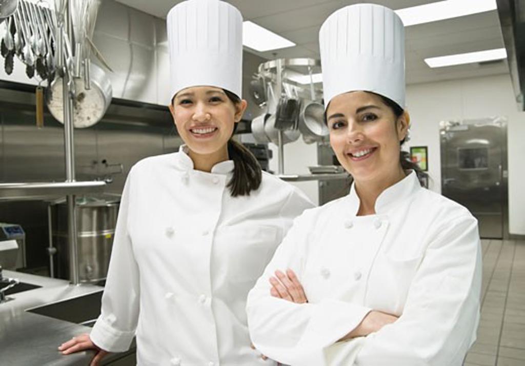 Female chefs posing in kitchen : Stock Photo