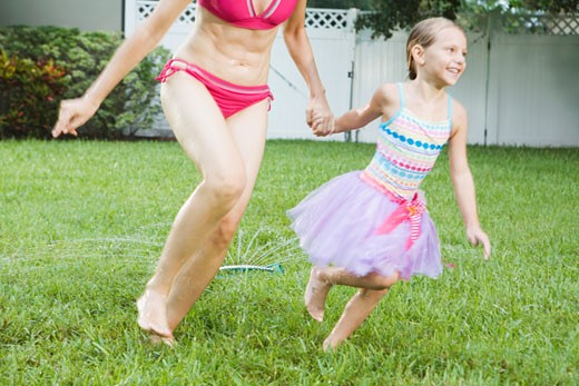 Mother and daughter running through sprinkler : Stock Photo