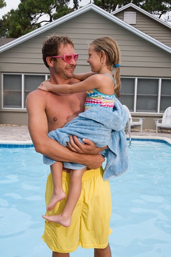 Father holding daughter by swimming pool : Stock Photo