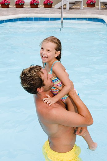 Father lifting daughter out of swimming pool : Stock Photo