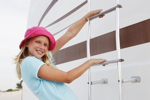 Girl climbing on motor home ladder : Stock Photo