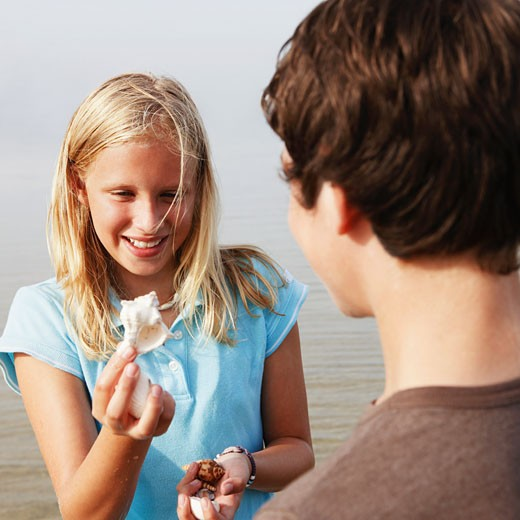 Girl showing shell to friend : Stock Photo