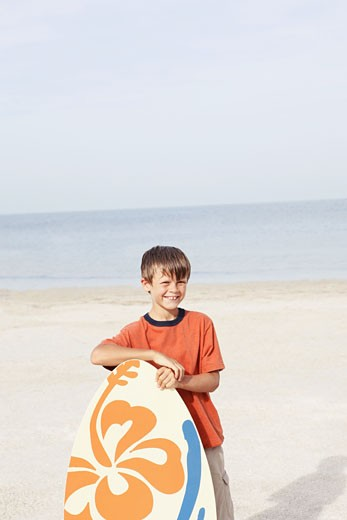 Stock Photo: 1795R-17217 Boy holding skimboard on beach