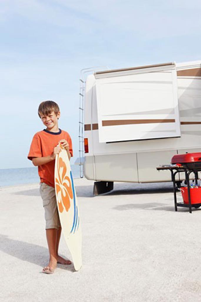 Stock Photo: 1795R-17218 Boy holding skimboard on beach