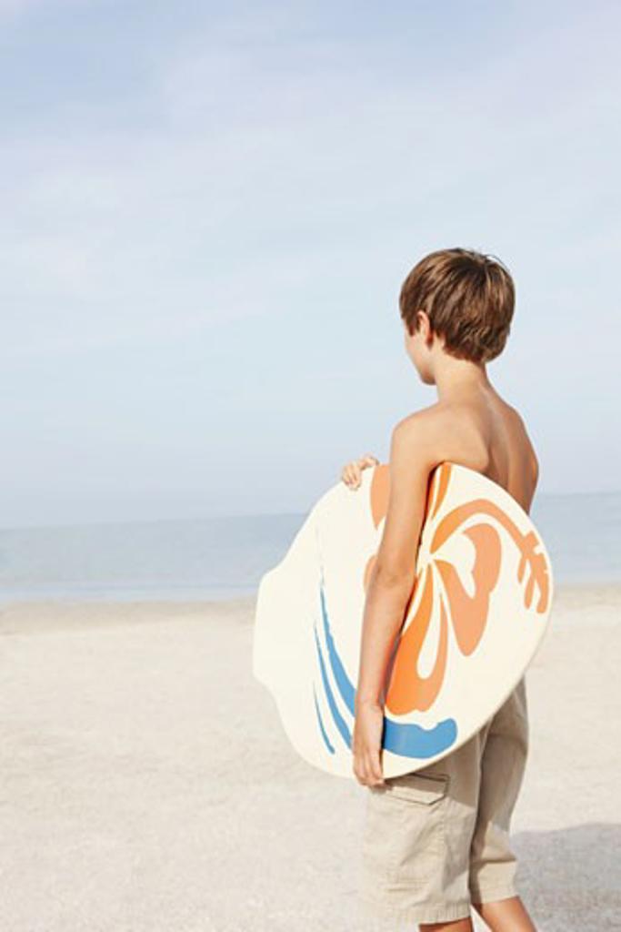 Boy holding skimboard on beach : Stock Photo