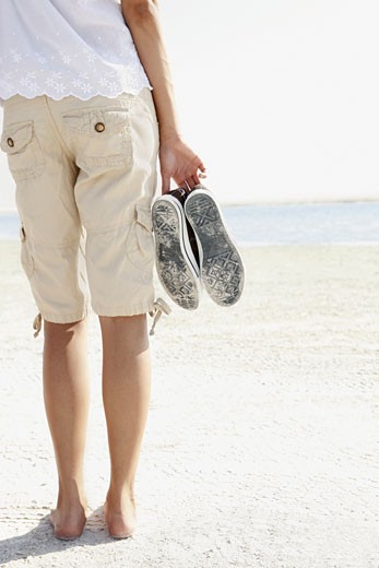Young woman walking barefoot on beach : Stock Photo