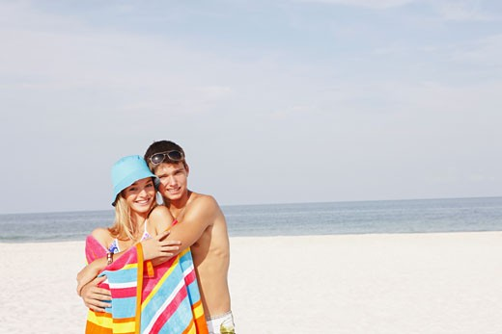 Stock Photo: 1795R-17377 Teenage couple hugging on beach