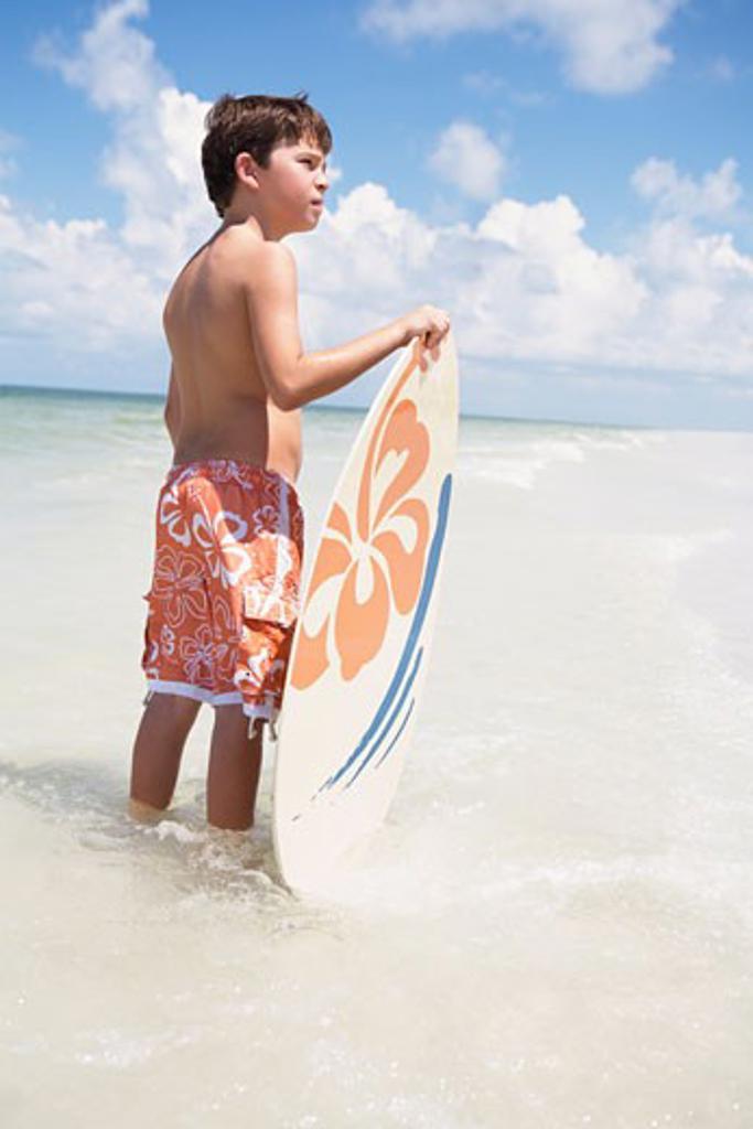 Stock Photo: 1795R-17463 Boy holding skimboard in ocean