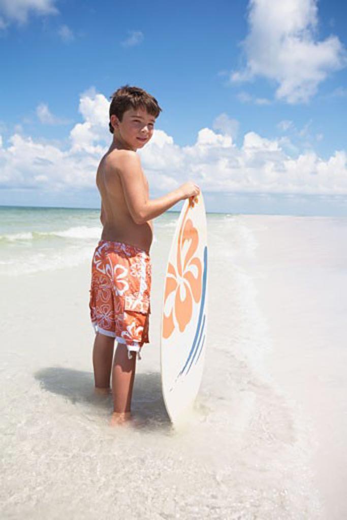 Boy holding skimboard in ocean : Stock Photo