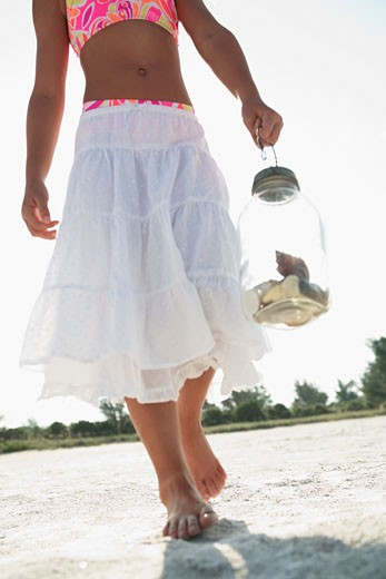 Girl on beach carrying jar of shells : Stock Photo