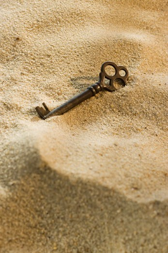 Stock Photo: 1795R-17863 Close up of old-fashioned key in sand
