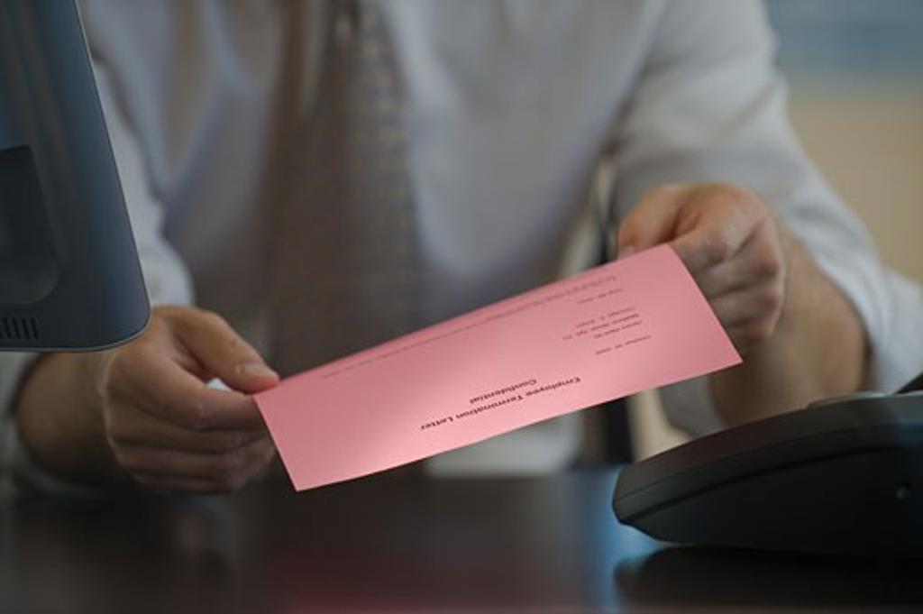 Man holding pink slip : Stock Photo