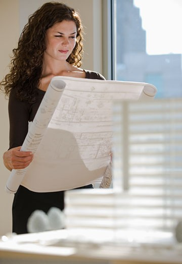 Architect viewing blueprints near building model : Stock Photo