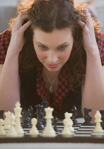 Stock Photo: 1795R-18099 Close up of woman looking down at chessboard