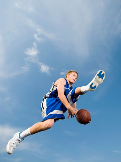 Teenage basketball player in mid-air with basketball : Stock Photo