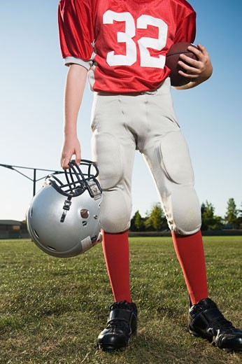 Football player holding helmet and football on field : Stock Photo