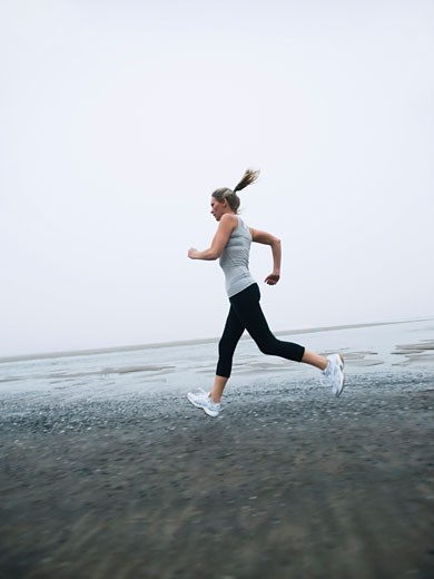 Woman jogging on foggy beach : Stock Photo