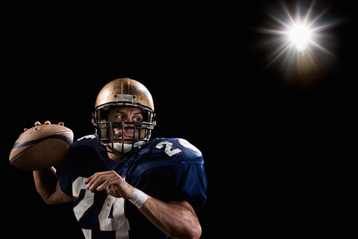 Quarterback throwing football : Stock Photo