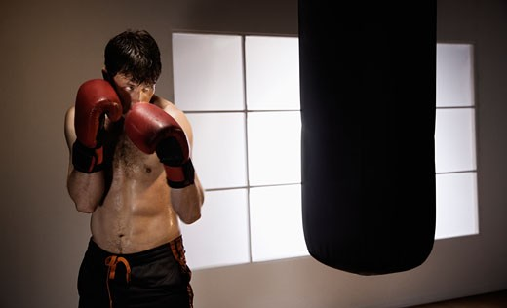 Boxer training with punching bag : Stock Photo