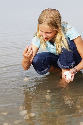 Girl finding seashells in ocean : Stock Photo
