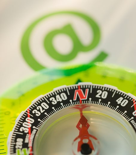 "Close up of compass and ""at"" symbol : Stock Photo"