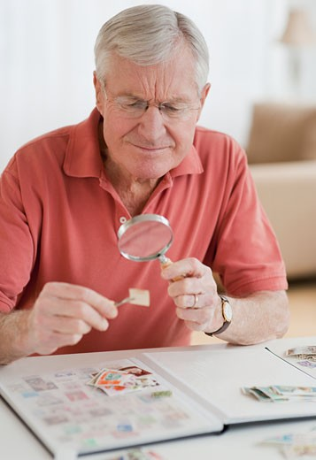 Stock Photo: 1795R-19500 Senior man looking at stamp collection