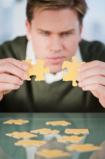 Businessman looking at puzzle pieces : Stock Photo